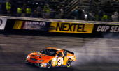 Robby Gordon trails smoke in the second turn during the NASCAR Nextel Cup Series Chevy American Revolution 400 at Richmond International Raceway May...