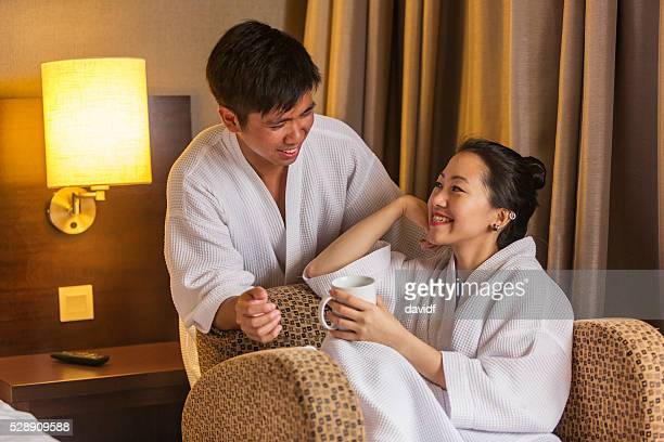 Robe Wearing Young Asian Couple With A Hot Drink