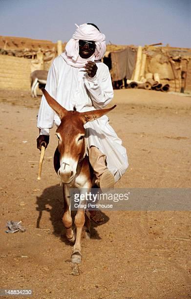 Robed man riding a donkey at camel market.