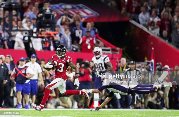 Robert Alford of the Atlanta Falcons runs past Tom Brady of the New England Patriots to score a touchdown on a 82 yard interception against the New...