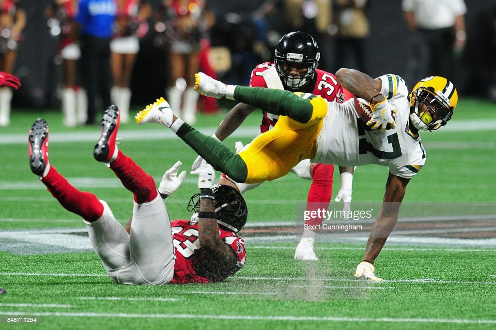 Robert Alford #23 of the Atlanta Falcons tackles Davante Adams #17 of the Green Bay Packers during the second half at Mercedes-Benz Stadium on September 17, 2017 in Atlanta, Georgia.