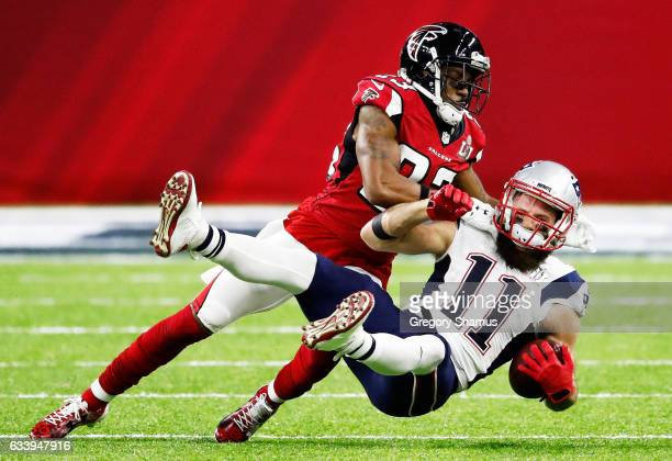 Robert Alford of the Atlanta Falcons tackles Julian Edelman of the New England Patriots in the first quarter of Super Bowl 51 at NRG Stadium on...