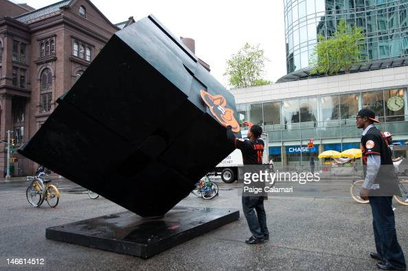Robert Andino of the Baltimore Orioles places the Oriole Bird on the Cube at Astor Place as teammate Adam Jones looks on Tuesday May 2 in New York...