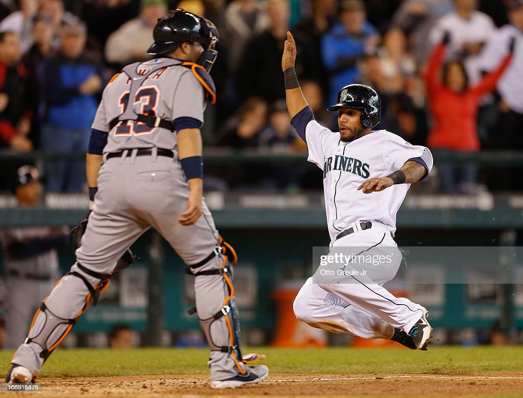 Robert Andino #3 of the Seattle Mariners scores on an RBI double by Kyle Seager in the seventh inning against catcher Alex Avila #13 of the Detroit Tigers at Safeco Field on April 18, 2013 in Seattle, Washington.