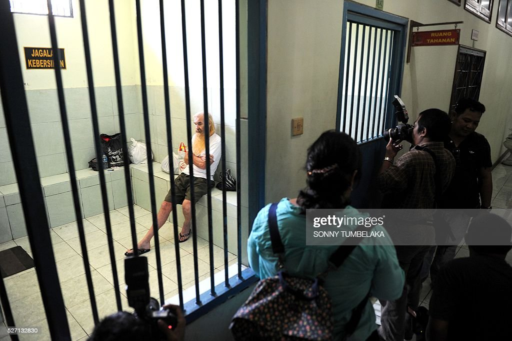 Robert Andrew Fiddel Ellis of Australia (L inside) sits in a holding cell at the prosecutor's office in Denpasar on Bali island on May 2, 2016. Ellis was arrested on January 11, accused of child sex offences in Bali. / AFP / SONNY