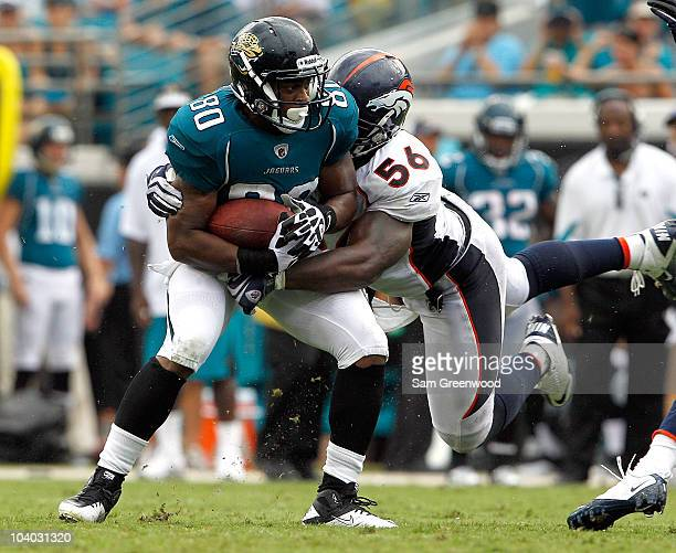 Robert Ayers of the Denver Broncos attempts to tackle Mike Thomas of the Jacksonville Jaguars during the NFL season opener game at EverBank Field on...