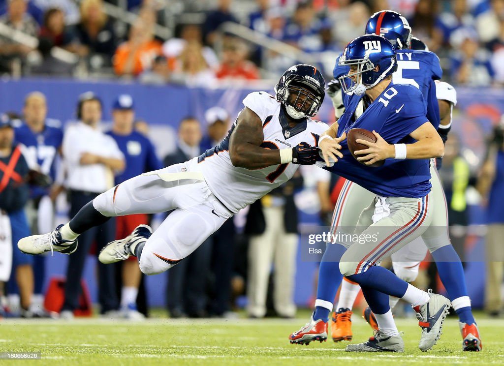 Robert Ayers #91 of the Denver Broncos tries to sack <a gi-track='captionPersonalityLinkClicked' href=/galleries/search?phrase=Eli+Manning&family=editorial&specificpeople=202013 ng-click='$event.stopPropagation()'>Eli Manning</a> #10 of the New York Giants in the fourth quarter at MetLife Stadium on September 15, 2013 in East Rutherford, New Jersey. The Denver Broncos defeated the New York Giants 41-23.