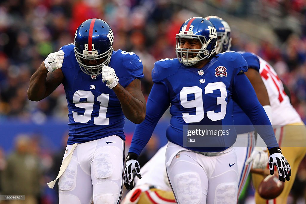Robert Ayers of the New York Giants celebrates after sacking Colin Kaepernick of the San Francisco 49ers in the first quarter as Mike Patterson of...