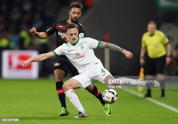 Robert Bauer of Bremen is challenged by Karim Bellarabi of Leverkusen during the Bundesliga match between Bayer 04 Leverkusen and Werder Bremen at...