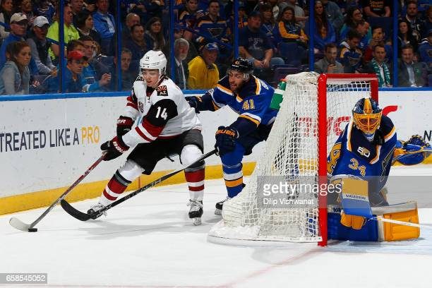 Robert Bortuzzo and Jake Allen of the St Louis Blues defend against Clayton Keller of the Arizona Coyotes at the Scottrade Center on March 27 2017 in...
