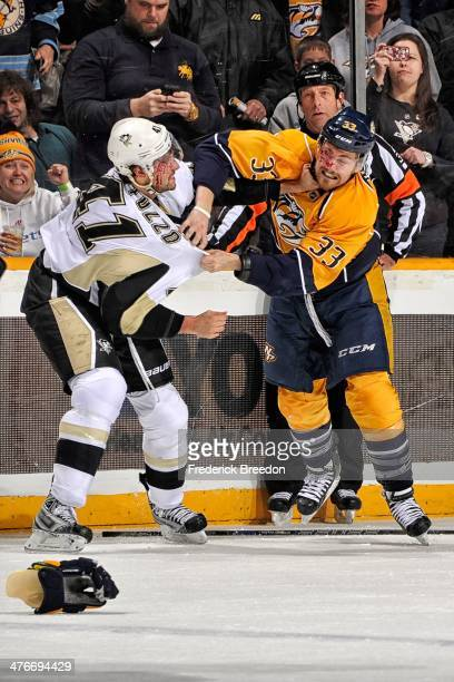 Robert Bortuzzo of the Pittsburgh Penguins fights Colin Wilson of the Nashville Predators at Bridgestone Arena on March 4 2014 in Nashville Tennessee