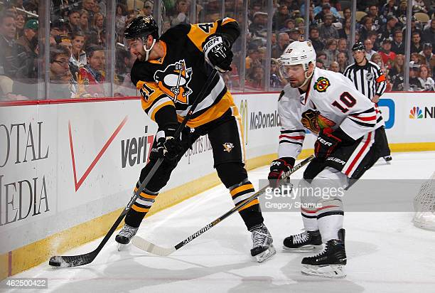 Robert Bortuzzo of the Pittsburgh Penguins moves the puck in front of Patrick Sharp of the Chicago Blackhawks at Consol Energy Center on January 21...