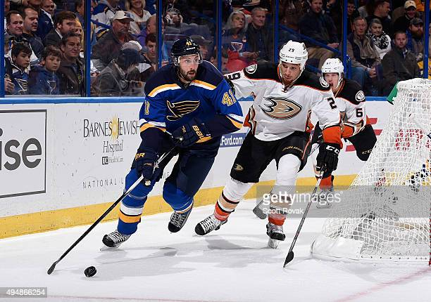 Robert Bortuzzo of the St Louis Blues handles the puck as Chris Stewart of the Anaheim Ducks defends on October 29 2015 at Scottrade Center in St...