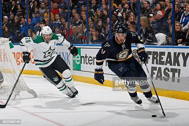 Robert Bortuzzo of the St Louis Blues handles the puck as Vernon Fiddler of the Dallas Stars gives chase on December 26 2015 at Scottrade Center in...