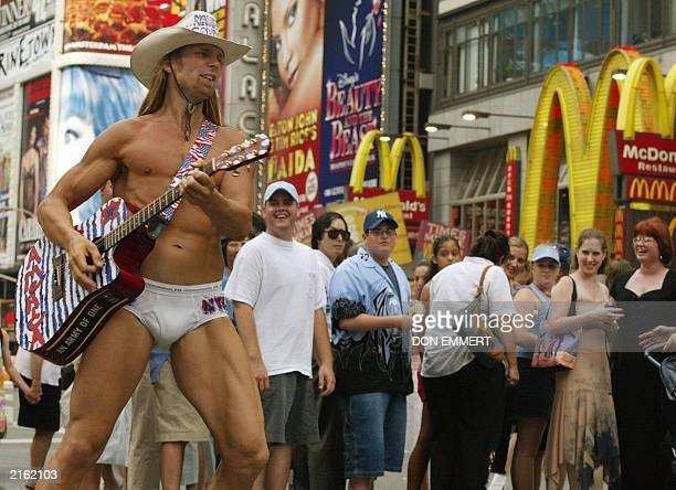 Robert Burck of Cincinnati OH who calls himself the Naked Cowboy plays his guitar at Times Square in New York 05 July 2003 and draws laughs from the...