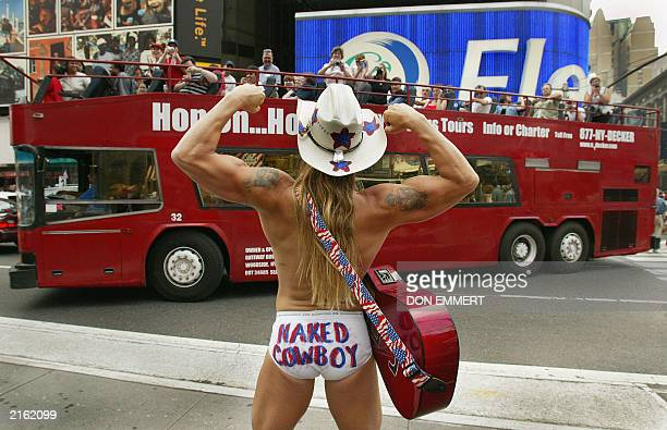 Robert Burck of Cincinnati who calls himself the Naked Cowboy strikes a pose for tourists on a bus in Times Square in New York 05 July 2003 Burck...