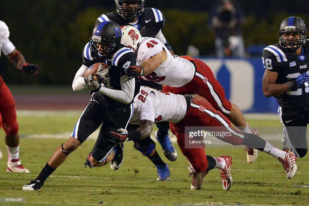 Robert Caldwell #48 and Jack Tocho #29 of the North Carolina State Wolfpack leap to tackle Johnell Barnes #4 of the Duke Blue Devils at Wallace Wade Stadium on November 9, 2013 in Durham, North Carolina. Duke defeated NC State 38-20.
