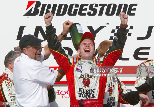 Robert Clarke of Honda sprays champagne over Andretti Green Racing driver Dan Wheldon after winning the Indy Racing League IndyCar Series Bridgestone...