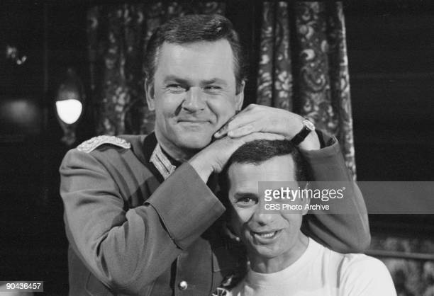 HEROES Robert Clary as Cpl Louis LeBeau below and Bob Crane as Col Robert E Hogan in between scenes of Klink Commandos an episode from CBS' comedy...