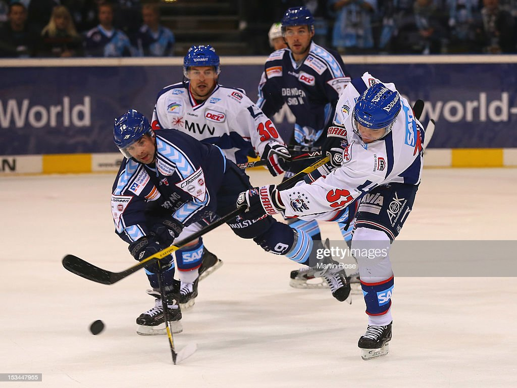 Robert Collins (L) of Hamburg battles for the puck with Janik Douglas (R) of Mannheim during the DEL match between Hamburg Freezers and Adler Mannheim at O2 World on October 5, 2012 in Hamburg, Germany.