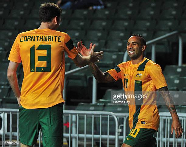 Robert Cornthwaite of Australia celebrates with teammate Archie Thompson during the 2013 EAFF East Asian Cup Qualifying match between Korea DPR and...