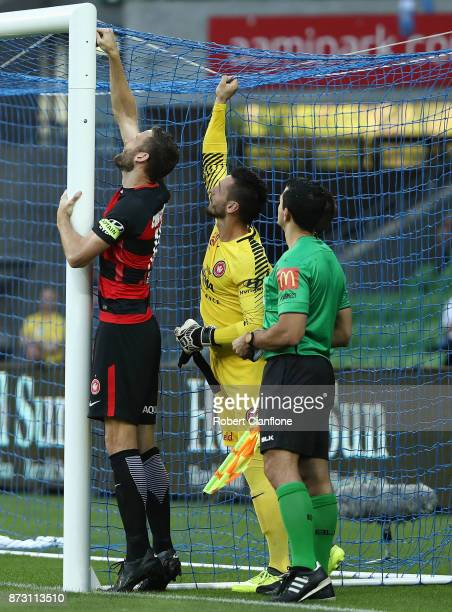 Robert Cornthwaite of the Wanderers and Western Sydney goalkeeper Verdran Janjetovic are asked by the officials to reattach the a part of the goal...