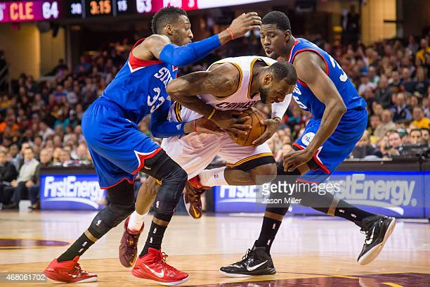 Robert Covington and Henry Sims of the Philadelphia 76ers try to stop LeBron James of the Cleveland Cavaliers during the second half at Quicken Loans...