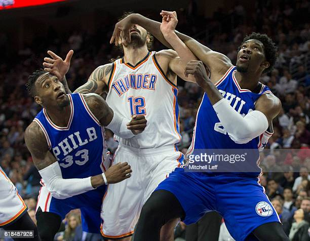 Robert Covington and Joel Embiid of the Philadelphia 76ers box out Steven Adams of the Oklahoma City Thunder during a foul shot in the fourth quarter...