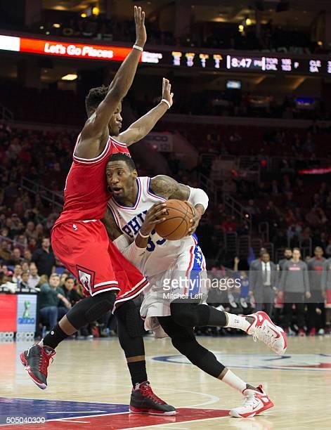 Robert Covington of the Philadelphia 76ers drives into Jimmy Butler of the Chicago Bulls on January 14 2016 at the Wells Fargo Center in Philadelphia...