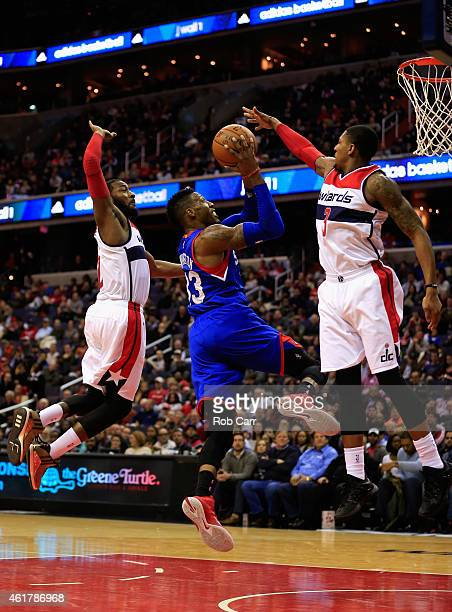 Robert Covington of the Philadelphia 76ers puts up a shot in front of John Wall and Bradley Beal of the Washington Wizards during the first half at...