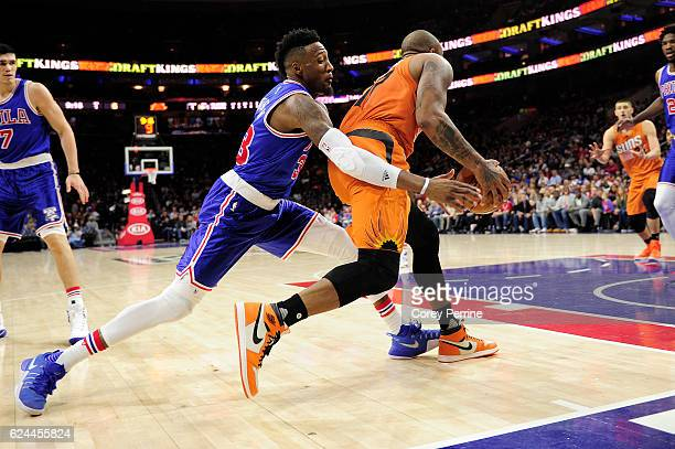 Robert Covington of the Philadelphia 76ers reaches around PJ Tucker of the Phoenix Suns during the first quarter at the Wells Fargo Center on...