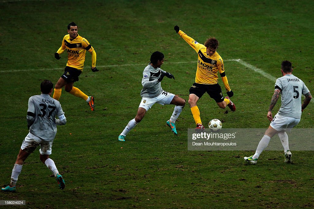 Robert Cullen of Venlo shoots and scores the third goal of the game as Theo Janssen (#5) and Patrick Van Aanholt (#38) of Vitesse attempt to stop him during the Eredivisie match between VVV Venlo and Vitesse Arnhem at the Seacon Stadion De Koel on December 9, 2012 in Venlo, Netherlands.
