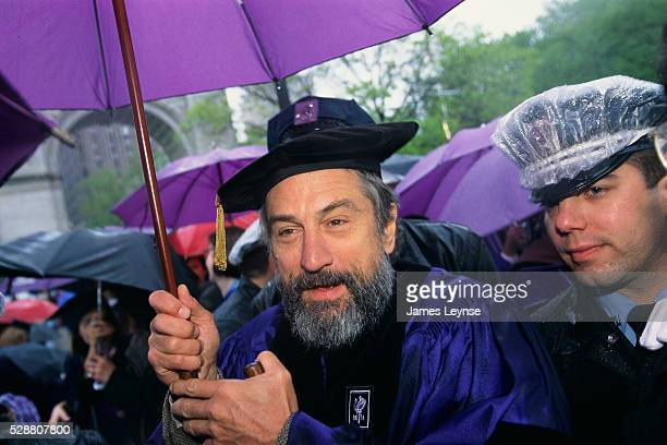 Robert De Niro holds an umbrella during the New York University graduation ceremony De Niro is receiving an honorary doctorate degree in fine arts...