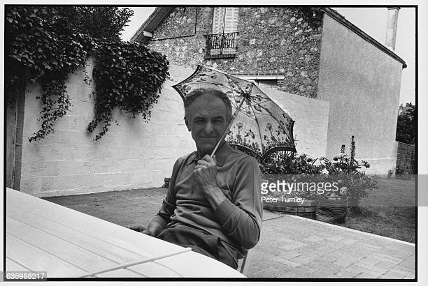 Robert Doisneau sits on a patio holding a tiny child's umbrella to shield his face from the sun