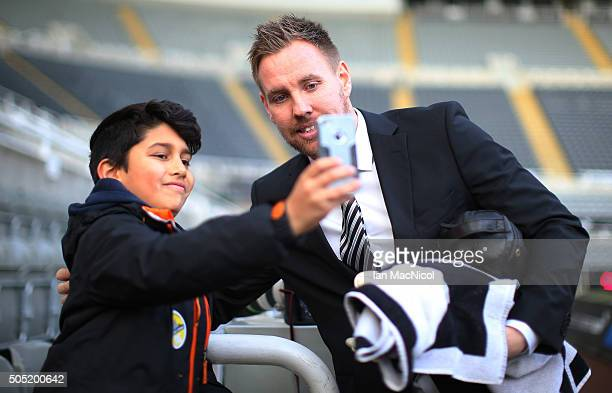 Robert Elliot of Newcastle United poses for photographs for a young fan on arrival at the stadium prior to the Barclays Premier League match between...