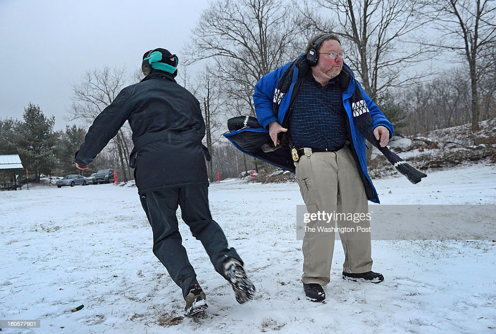 Robert Farago on a dead run while friend David Kenik tries his fastest response to draw his gun and shoot at a range in Manville, RI on January 28, 2013. The pair are demonstrating the Tueller Drill, an exercise in self-defense training that measures response time and distance with a holstered gun. Farago blogs for a successful website, thetruthaboutguns.com which saw its readership double since talk of banning automatic assault weapons in the U.S.