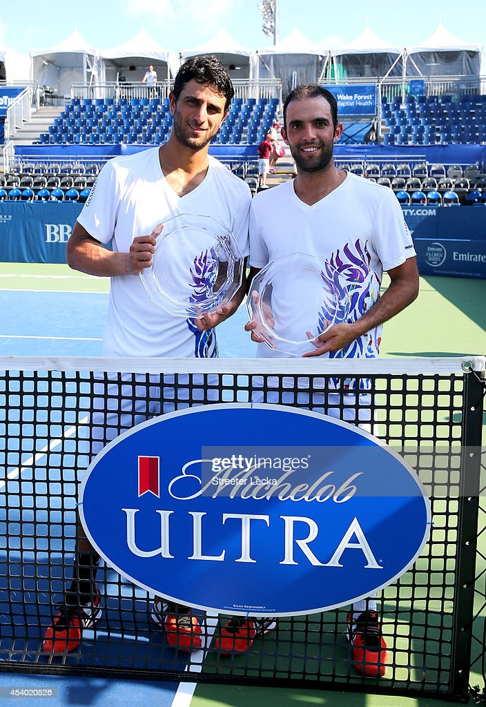 Robert Farah of Colombia and his teammate Juan Sebastian Cabal of Colombia celebrate with the trophy after defeating Jamie Murray of Great Britain and teammate John Peters of Australia during the men's doubles finals match of the Winston-Salem Open at Wake Forest University on August 23, 2014 in Winston Salem, North Carolina.