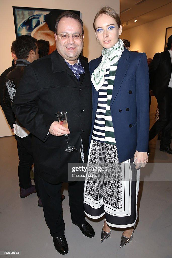 Robert Galstian (L) and Olga Sorokina visit the Mario Testino opening at PRISM during Academy Awards week on February 23, 2013 in Los Angeles, California.