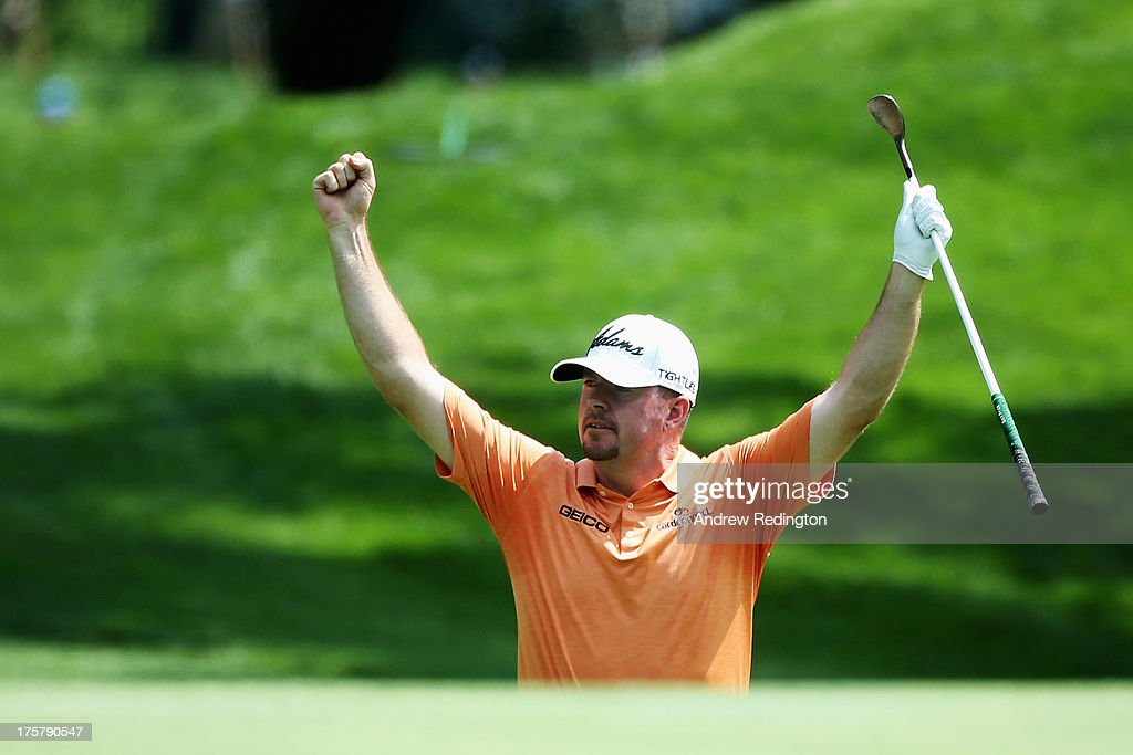 Robert Garrigus of the United States celebrates chipping in for birdie on the ninth hole during the first round of the 95th PGA Championship on August 8, 2013 in Rochester, New York.