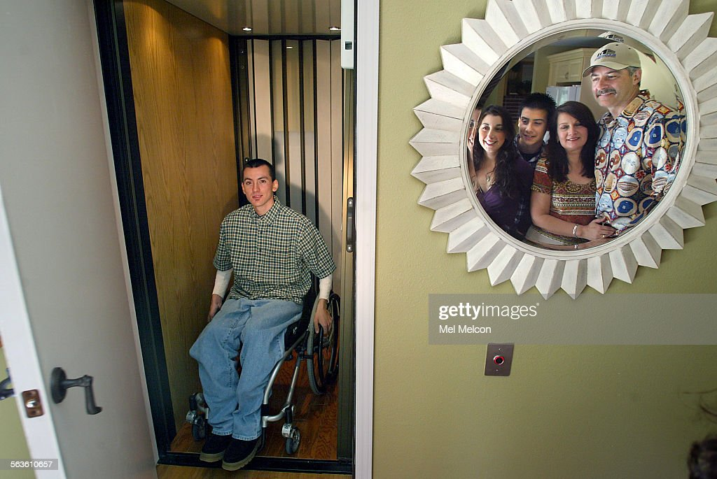 home chair elevator. robert gil, 23, sits on his wheel chair while inside elevator at home