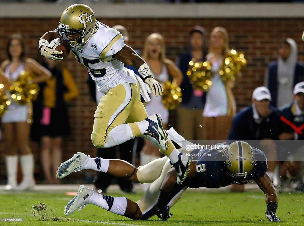 Robert Godhigh #25 of the Georgia Tech Yellow Jackets leaps over K'Waun Williams #2 of the Pittsburgh Panthers as he scores a touchdown at Bobby Dodd Stadium on November 2, 2013 in Atlanta, Georgia.