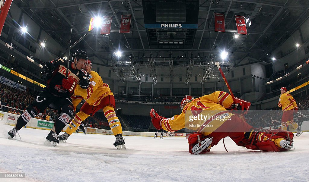 Robert Goepfert, goaltender of Duesseldorf makes a save on Christpher Herperger (L) of Hannover during the DEL match between Hannover Scorpions and Duesseldorfer EG at TUI Arena on November 23, 2012 in Hanover, Germany.