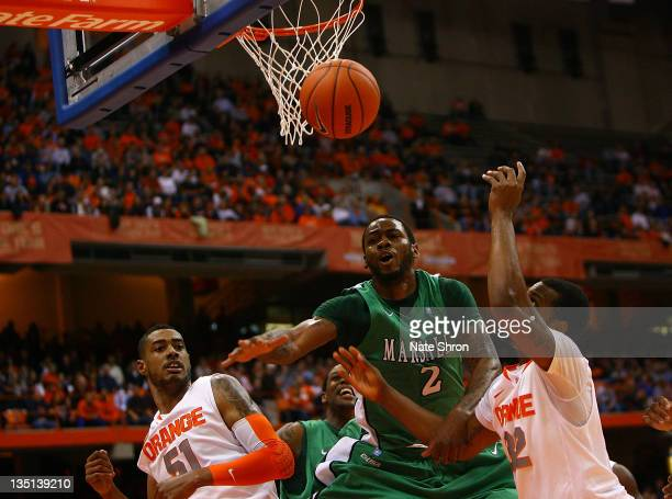 Robert Goff of the Marshall Thundering Herd reaches for the ball under the basket with Fab Melo and Kris Joseph of the Syracuse Orange during the...