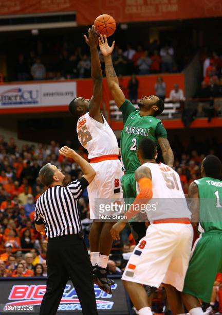 Robert Goff of the Marshall Thundering Herd reaches for the tip off against Rakeem Christmas of the Syracuse Orange at the start of the game at the...