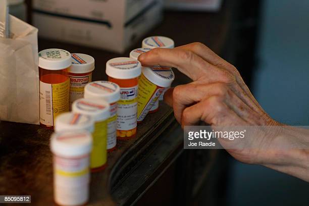 Robert Granville reaches for a medicine bottle as he takes his prescription pills on February 25 2009 in Miami Florida Because of budget constraints...