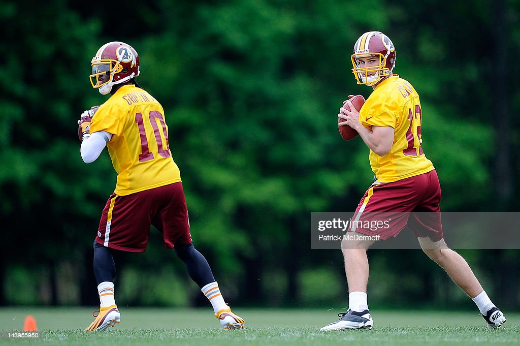 Robert Griffin III #10 and Kirk Cousins #12 of the Washington Redskins drop back to throw a pass during the Washington Redskins rookie minicamp on May 6, 2012 in Ashburn, Virginia.