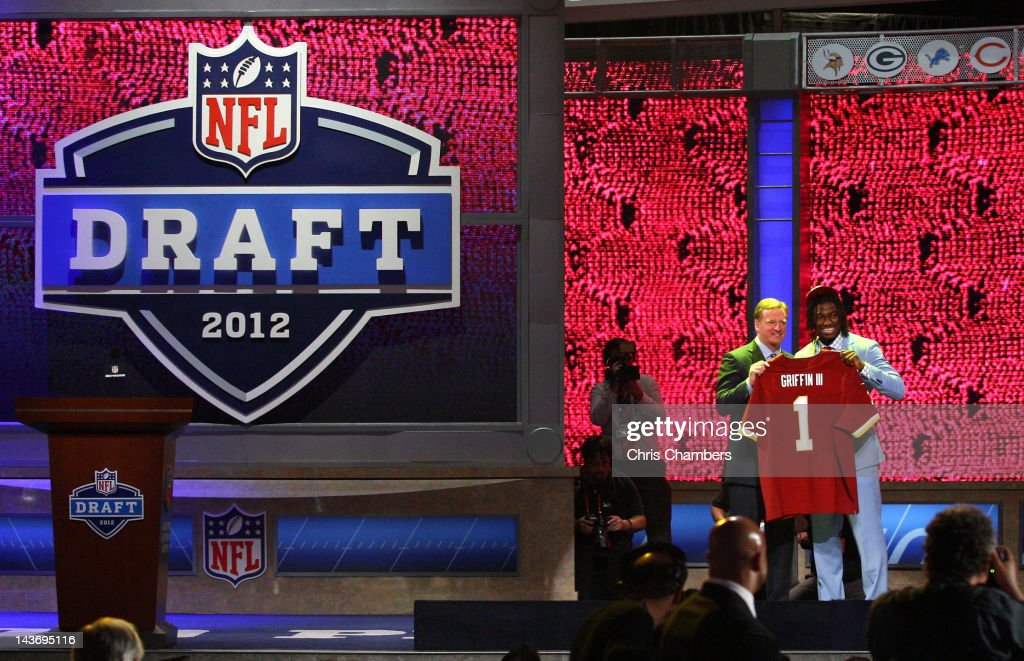 Robert Griffin III (R) from Baylor holds up a jersey as he stands on stage with NFL Commissioner Roger Goodell after Griffin was selected #2 overall by the Washington Redskins in the first round of the 2012 NFL Draft at Radio City Music Hall on April 26, 2012 in New York City.