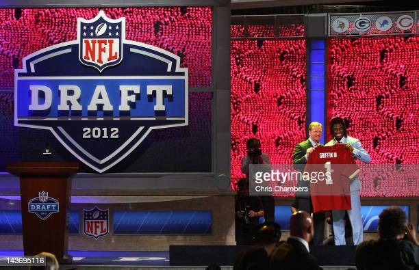 Robert Griffin III from Baylor holds up a jersey as he stands on stage with NFL Commissioner Roger Goodell after Griffin was selected overall by the...