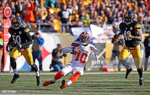 Robert Griffin III of the Cleveland Browns slides to avoid being tackled by Ryan Shazier of the Pittsburgh Steelers and Bud Dupree in the first half...