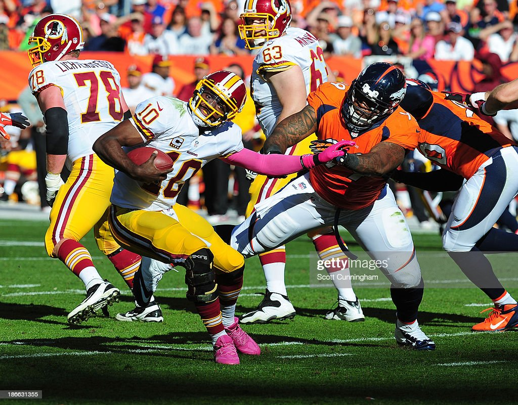 Robert Griffin III #10 of the Washington Redskins is pursued by Kevin Vickerson #99 of the Denver Broncos at Sports Authority Field on October 27, 2013 in Denver, Colorado.